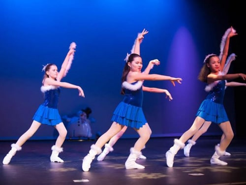 Four Dancers dressed in blue onstage